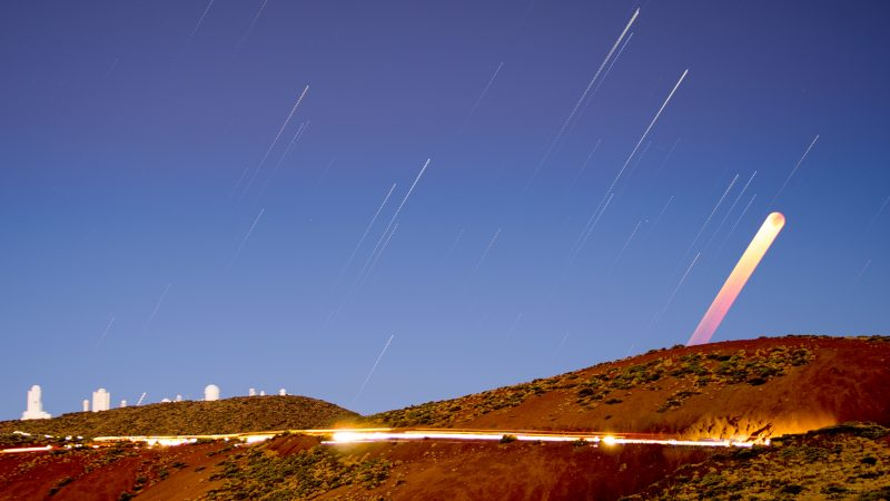 Yellow-orange wide streak with white star trails, observatory in background.