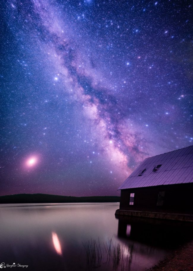 Long exposure photo with big dot of Mars and its reflection in a lake, and Milky Way soaring above.
