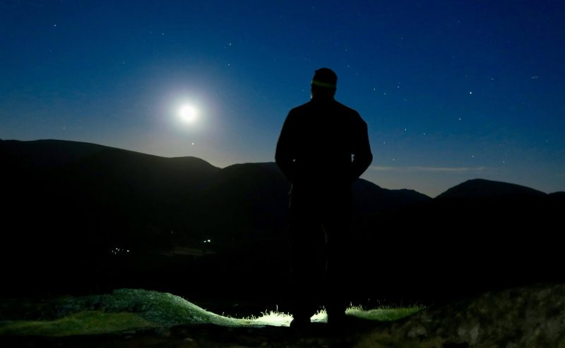Silhouetted man looking at sky with bright moon and a few tiny faint dots.