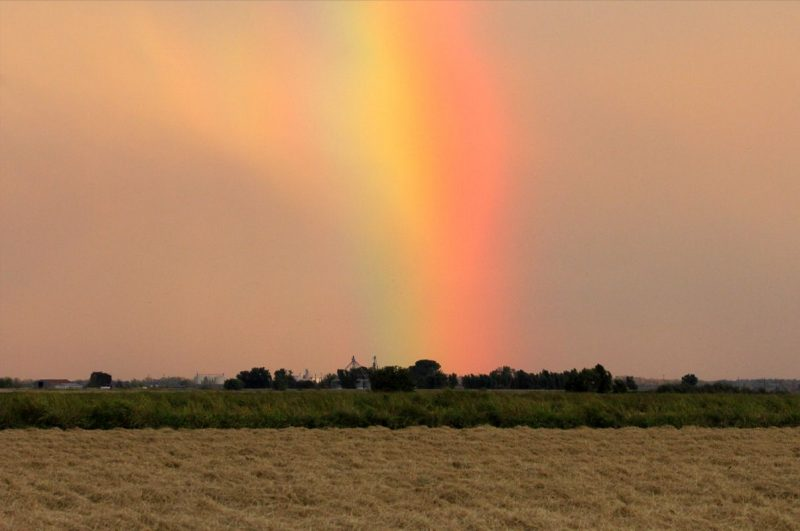 Rainbow touching horizon, with colored virga to one side.