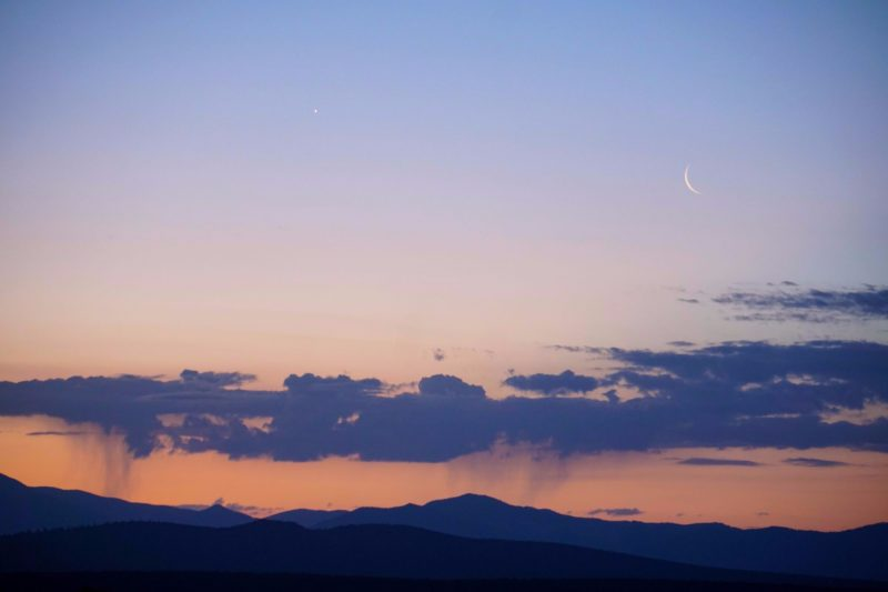 Waning moon, Venus, virga in orange-pink sky, over a mountain silhouette.
