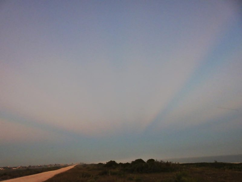 Pink rays converging in twilight with a road going into the distance.
