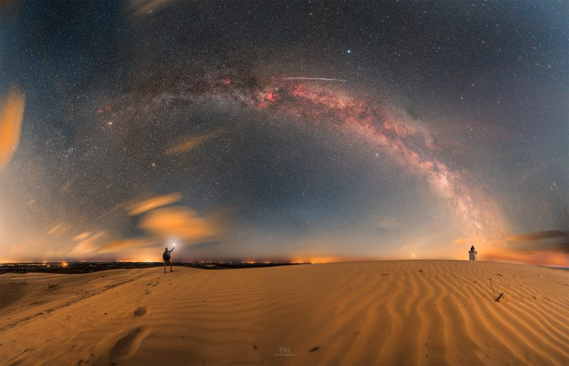 Milky Way arching over wide expanse of sand, with man standing in distance holding up a light.