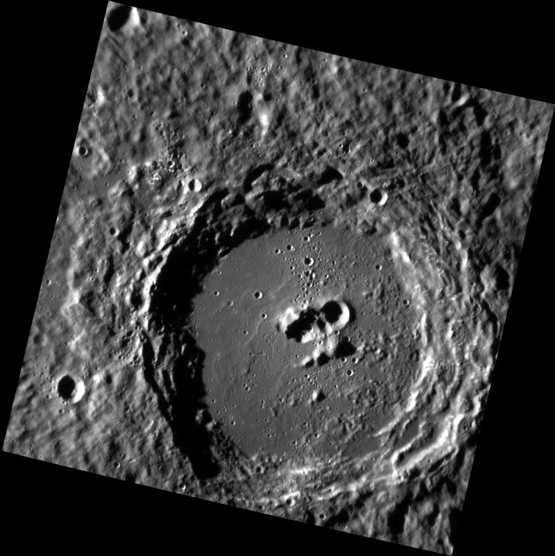 Stark black and white orbital image of a crater with peaks and indentations on crater floor.