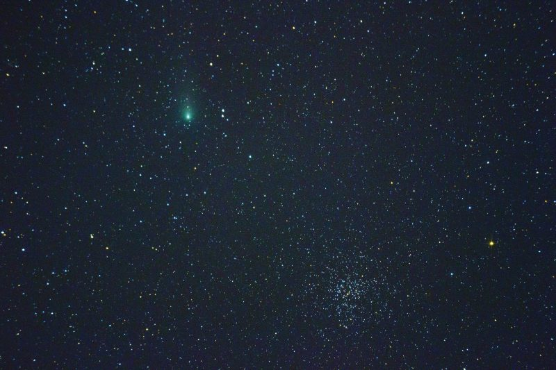 Star field with fuzzy green spot and small slightly oblong cluster of very many stars.