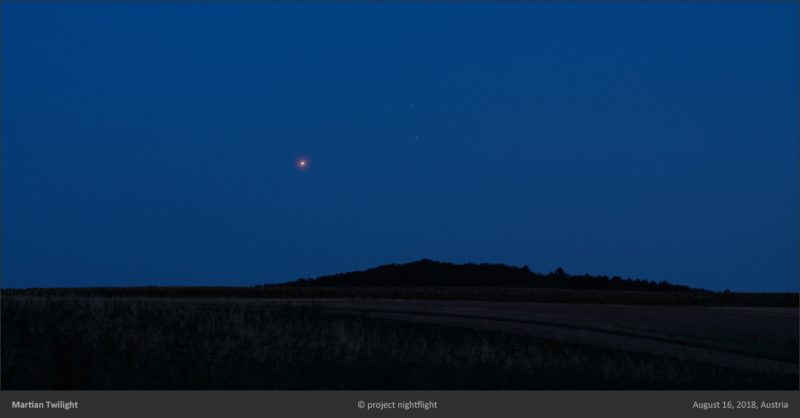 Dark twilight sky with shining red dot above a long low hill.