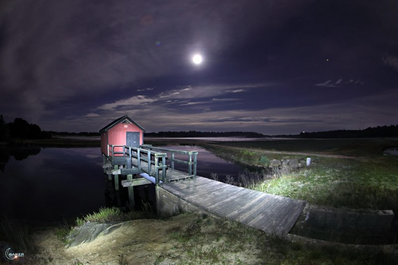 Short pier into pond with red shed on the end in a brightly moonlit landscape.