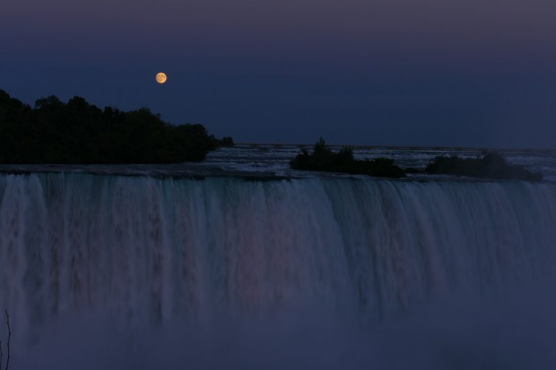 Dim photo of huge wide waterfall and glowing yellow full moon above.