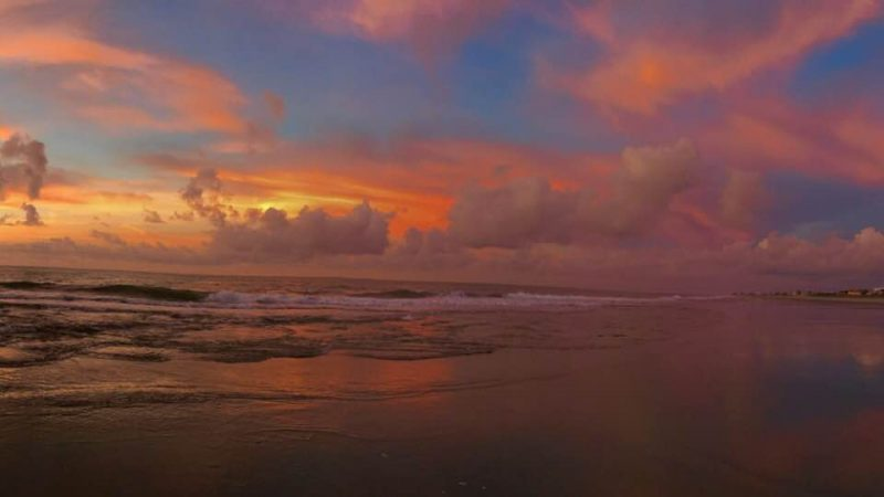 Orange-yellow sunrise through puffy clouds above a beach with incoming waves.