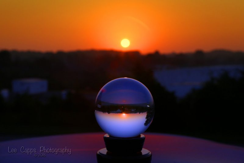 Glowing yellow sun on horizon lined up with crystal ball on a table.