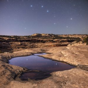 Desert scene with bright stars above and reflected in a pool among rocks and mesas.