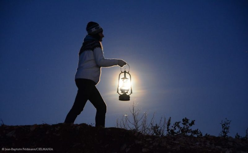 A woman walking with a glass lantern, with the full moon appearing to light up the lantern.