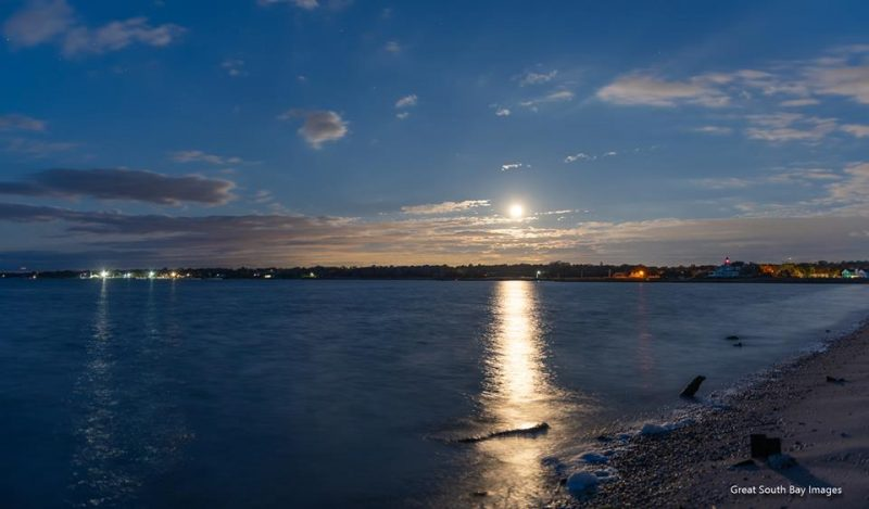 Small, fuzzy, bright full moon with long reflection in sea.