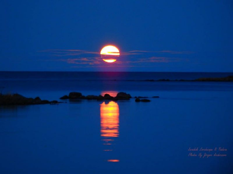 Full moon striped with clouds and reflected in waters of rocky seacoast.