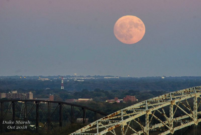 Giant pink full moon over tall, rusty trestles.