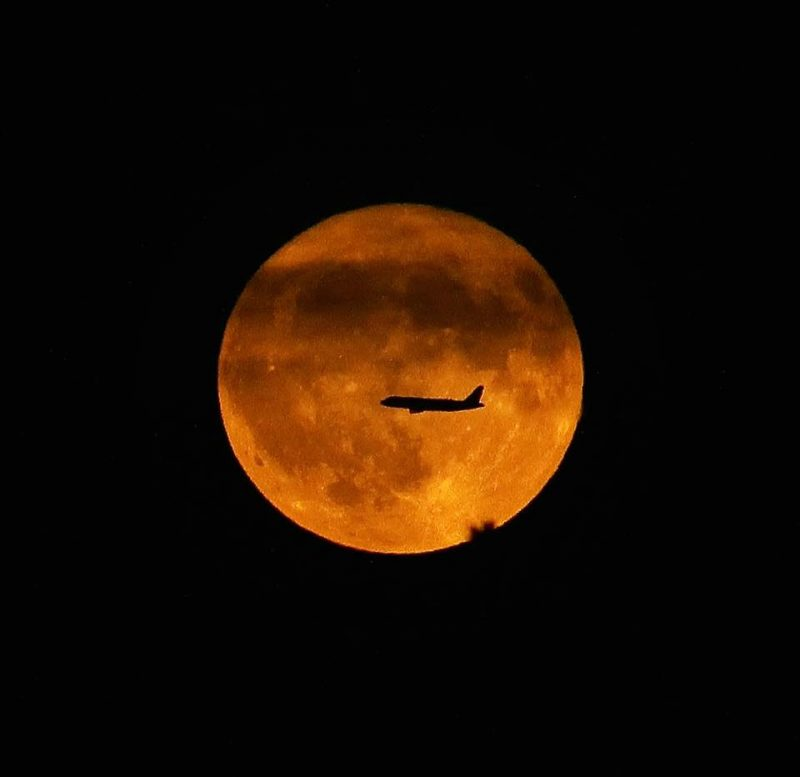Jetliner silhouetted against giant orange full moon.