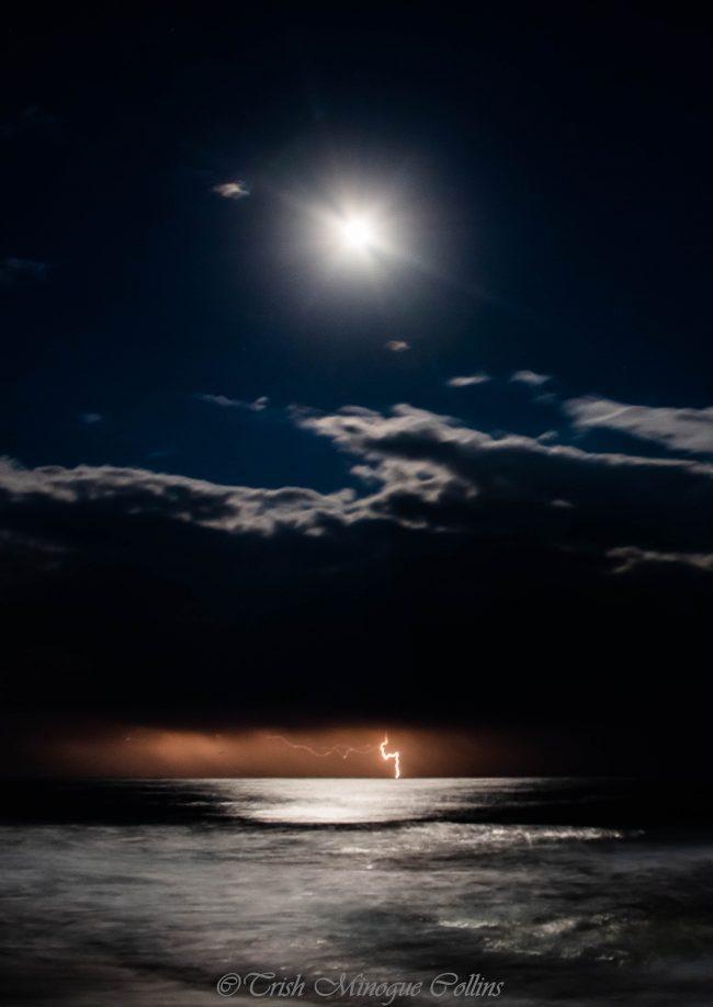 Identical lightning bolt under moon shining through clouds above silvery ocean.