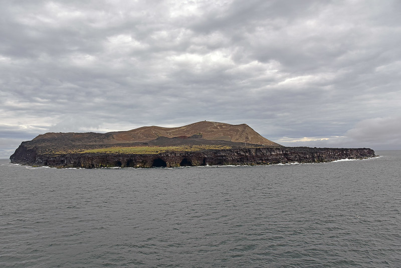 A photo of Surtsey taken from a boat. The island is mostly dark brown with some areas of green.