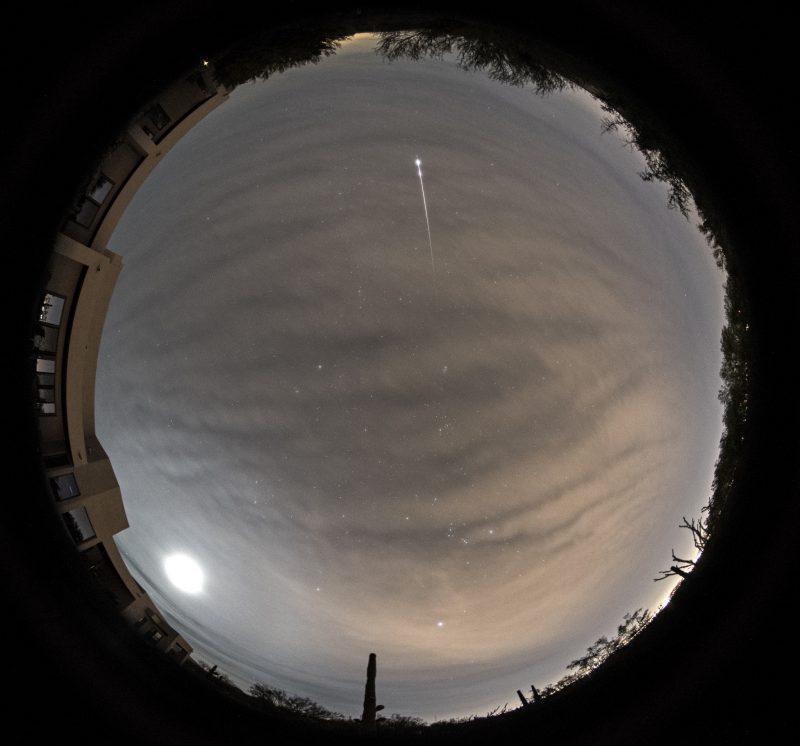 Round full-sky panorama with bright streak and large spot of light near horizon.
