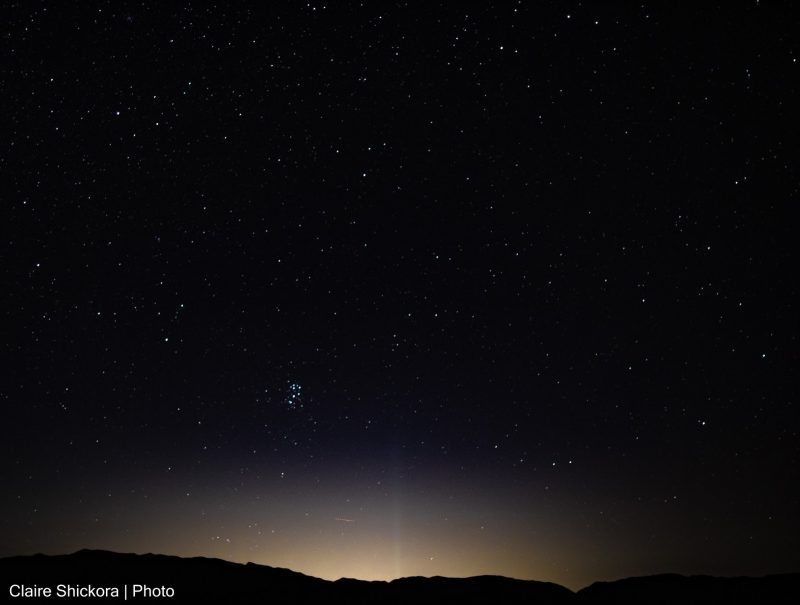 Starry sky with small distinct cluster of stars near the horizon's glow.