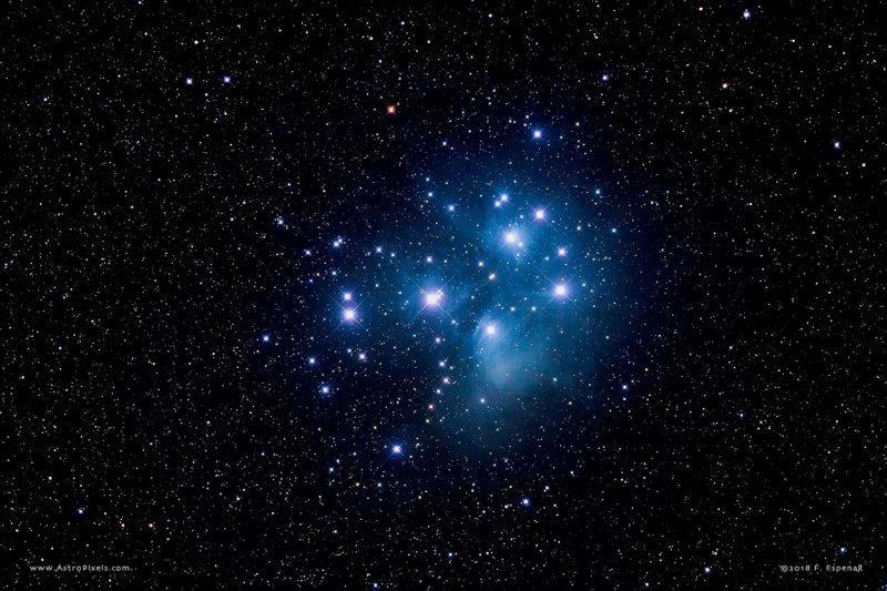 Brilliant blue-white stars in bluish mist against starfield.