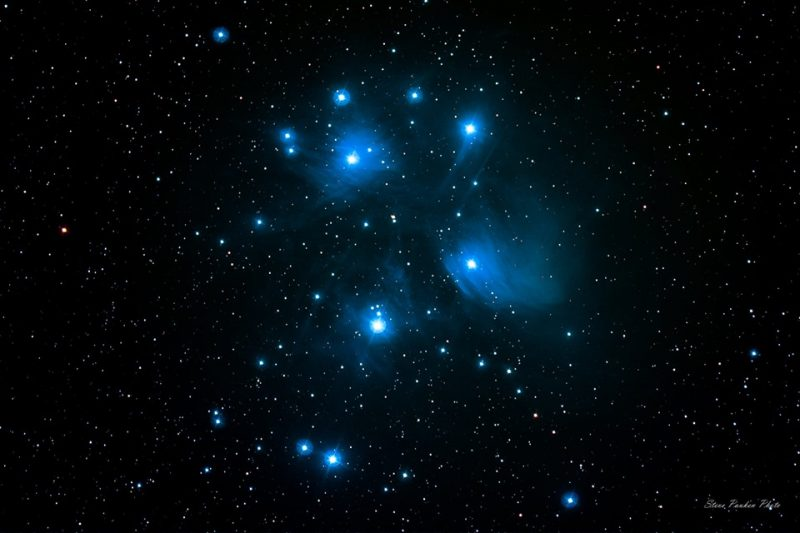 Several bright white stars in glowing blue patches against a starry background.