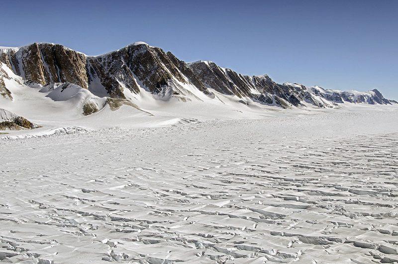 glacier next to rocky hills