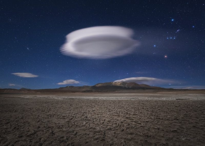 Saucer-shaped cloud hanging solitary above flat cracked brown desert.