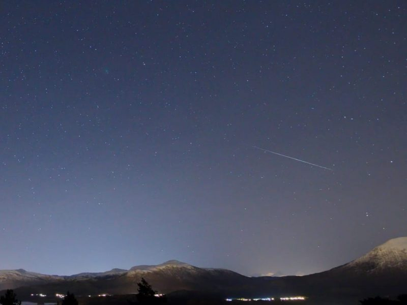 Starry sky with faint, straight white streak and small fuzzy white dot.