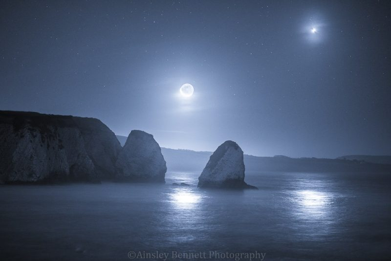 Bright moon and planet over rocky cliff coast with very big rock in the sea.