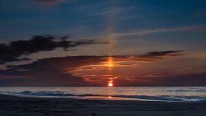 Orange sun rising over the ocean, with sun pillar above.