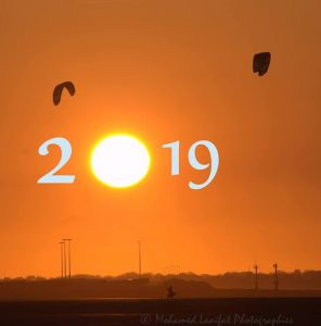 The numbers 2019 in a superimposed on a photo of orange skies over Normandy. France.