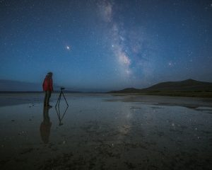 A person in a red jacket photographing the night sky. Milky Way stars reflecting in desert's dry lake bed.