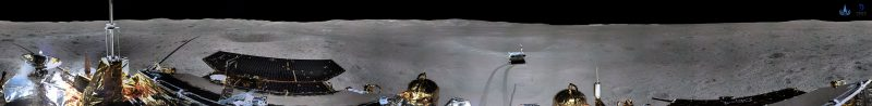 Wide photo of gray lunar landscape, black sky, bright sunlight. Top of lander visible across bottom of photo.