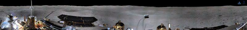 Wide photo of gray lunar landscape, black sky, bright sunlight. Top of lander visible across bottom of photo.