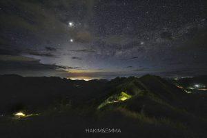 Bright planets over dark mountainous landscape