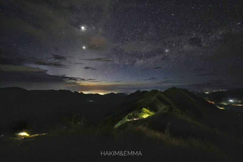Bright planets over dark mountainous landscape