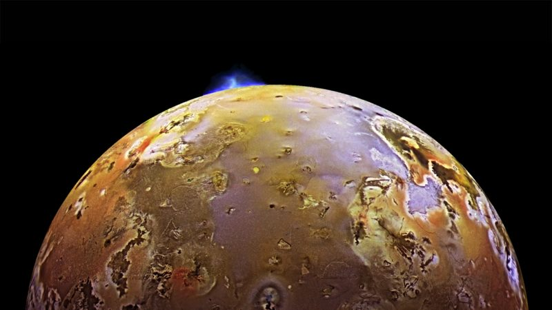 A blue geyser-like volcanic eruption at the edge of Io.