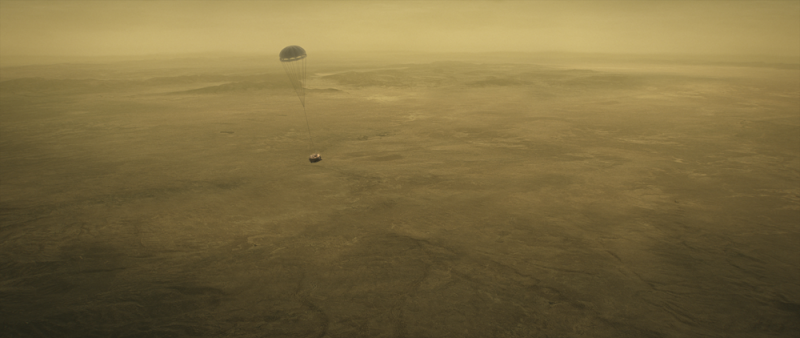 Small machine suspended from parachute in foggy atmosphere above yellowish landscape.