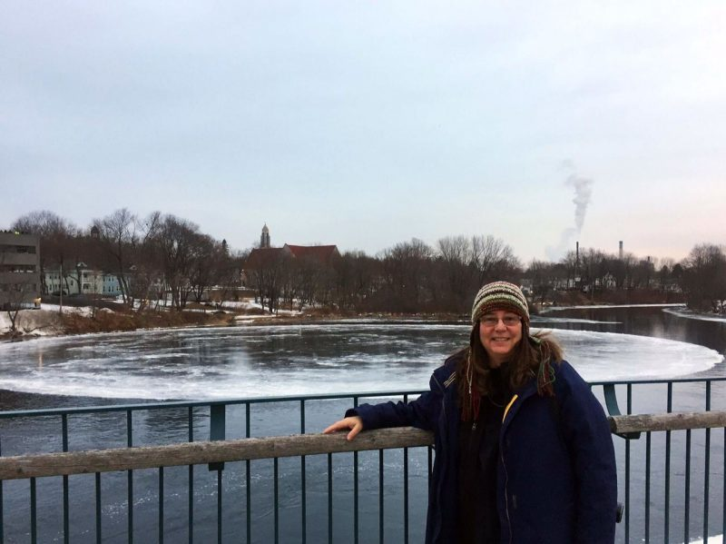 Large, circular ice disk nearly fills the river from bank to bank. Woman in winter clothes is standing in front of it.