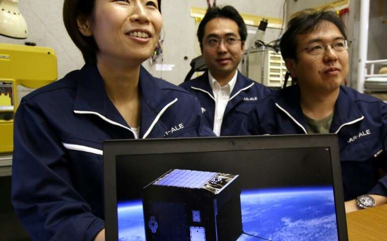 Japanese woman and two men in A.L.E. jackets, picture of cube sat on screen in foreground.