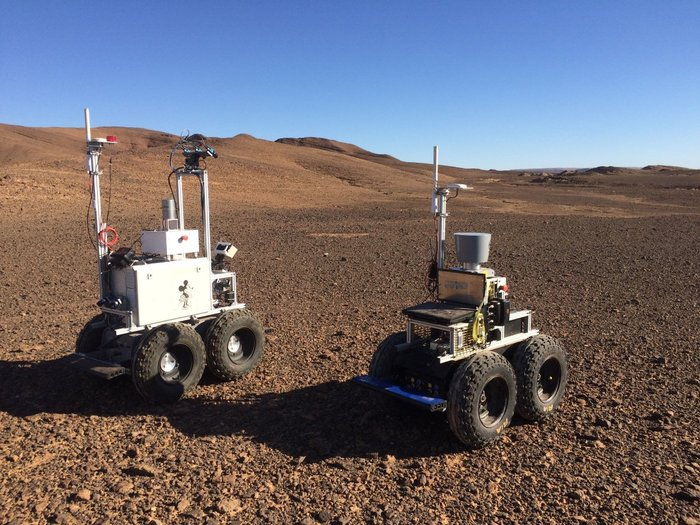 Two small boxy four-tired rovers with antennas on top