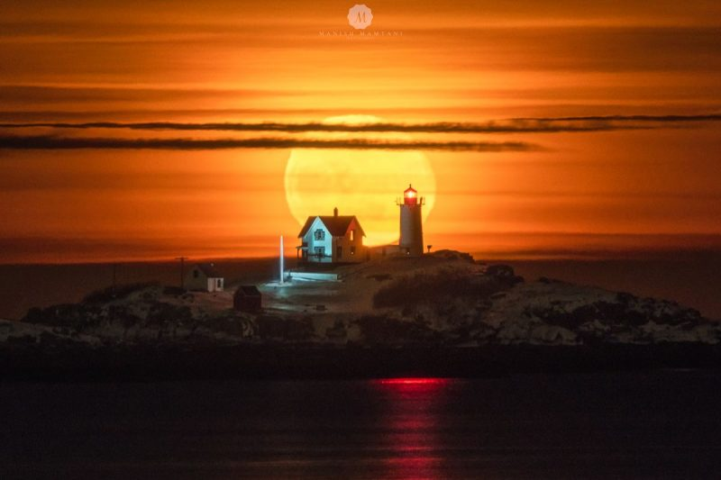 Giant yellow moon behind tall, distant lighthouse and lighthouse-keeper's Victorian residence.