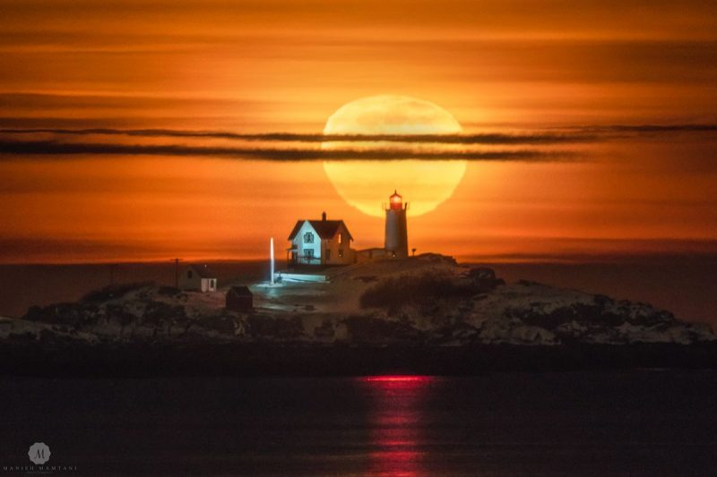 Giant yellow moon appears directly behind distant lighthouse.