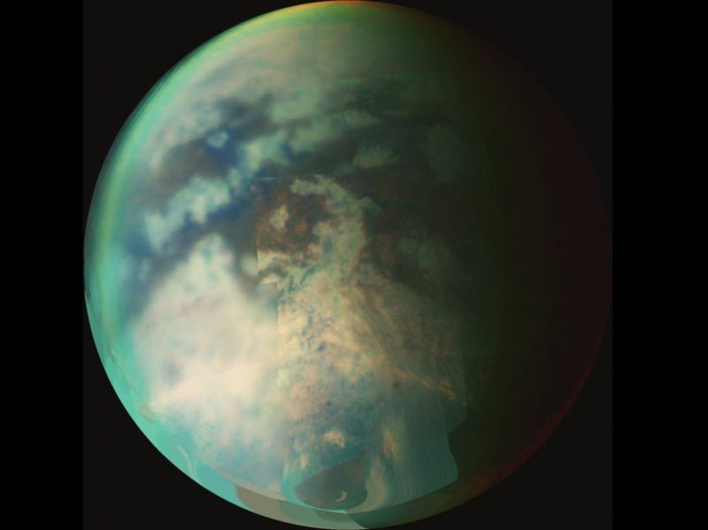 Blue-green Earth-like sphere with dark irregular light and dark surface features.
