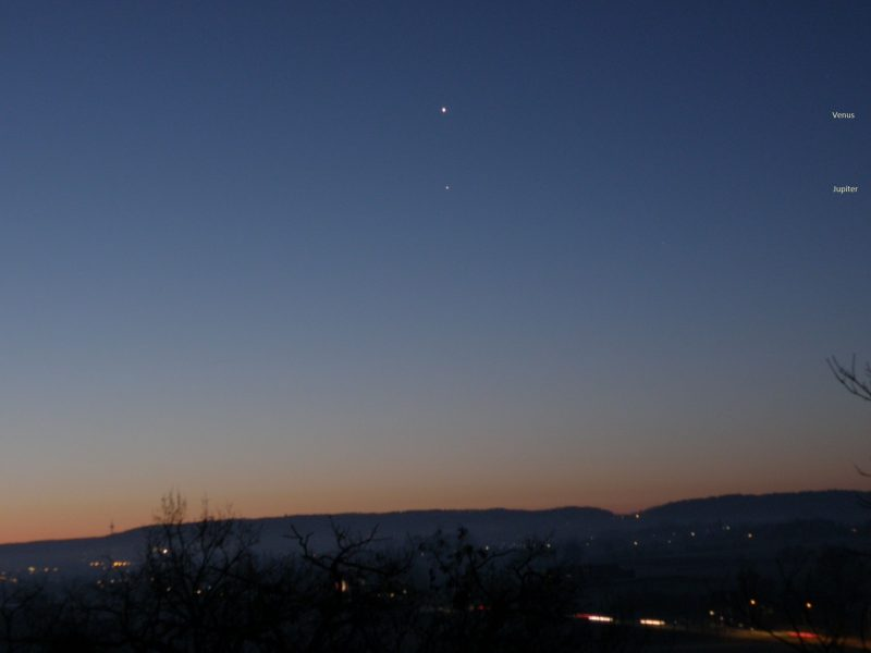 Two tiny dots in a bluish sky with a pink-orange horizon