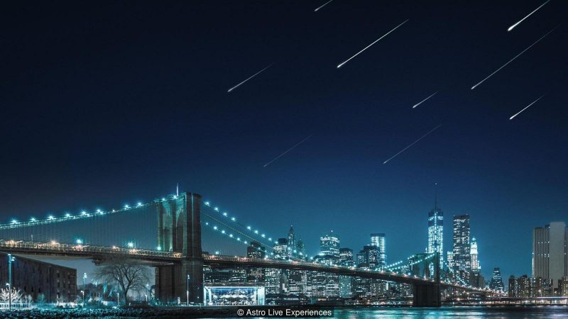 A lighted bridge, cityscape in background, with artificial meteors in the sky.