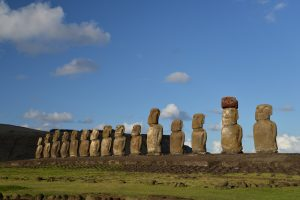 A line of huge Easter Island stone monuments against a blue sky