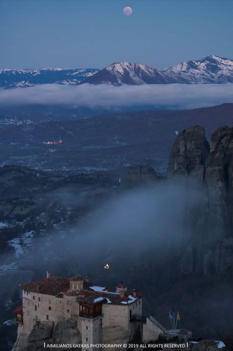 Twilight and haze over hilltop monastery, with the eclipsed moon over mountains in background.