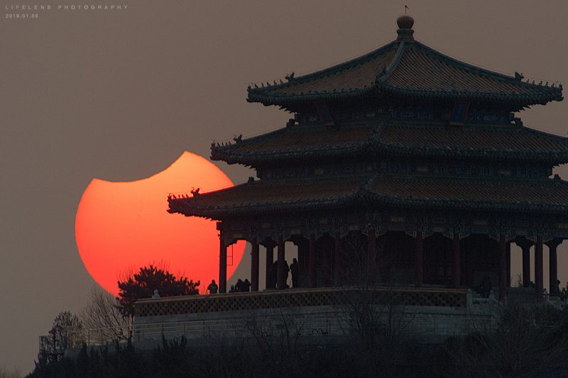 sun with bite out of it next to pagoda-like Chinese building